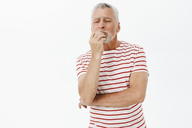 Tevreden oude man op vakantie complimenteert heerlijk eten, reageert op perfectie
