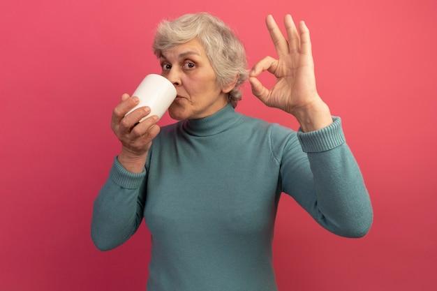 Tevreden oude vrouw met blauwe coltrui die een kopje thee drinkt en een goed teken doet dat op een roze muur is geïsoleerd