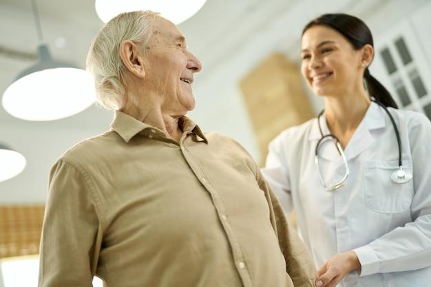 Tevreden oudere man die naar een vrouw in witte laboratoriumjas kijkt die hem thuis bezoekt