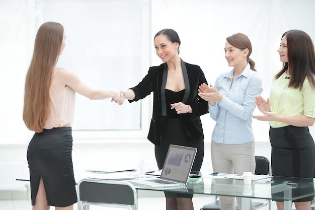 Tevreden oudere vrouw en jonge manager handenschudden na ondertekening contract op kantoor.