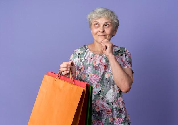 Tevreden oudere vrouw legt hand op kin met papieren boodschappentassen en kijkt omhoog geïsoleerd op paarse muur