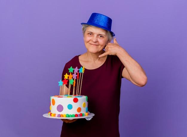 Tevreden oudere vrouw met feestmuts gebaren bel me teken en houdt verjaardagstaart geïsoleerd op paarse muur