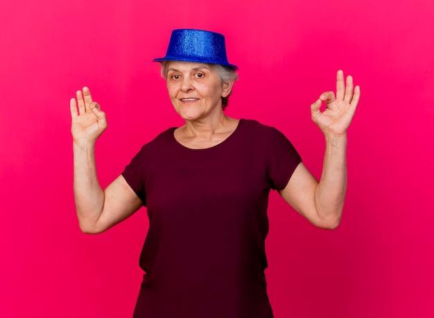 Tevreden oudere vrouw met feestmuts gebaren ok handteken met twee handen op roze