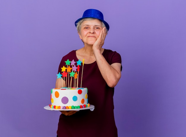 Tevreden oudere vrouw met feestmuts legt hand op gezicht en houdt verjaardagstaart geïsoleerd op paarse muur