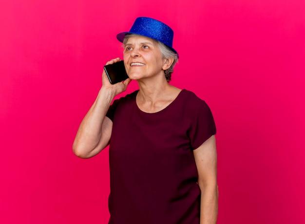 Tevreden oudere vrouw met feestmuts praat over de telefoon op roze
