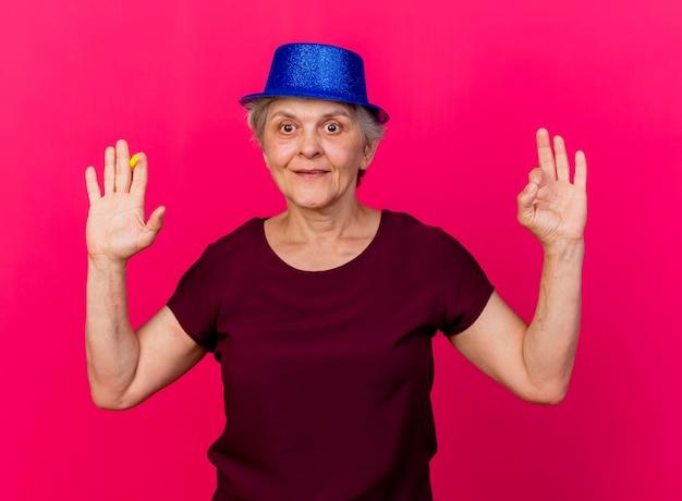 Tevreden oudere vrouw met feestmuts staat met opgeheven hand met fluitje en gebaren ok handteken geïsoleerd op roze muur