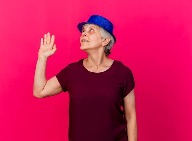 Tevreden oudere vrouw met feestmuts staat met opgeheven hand opzoeken op roze
