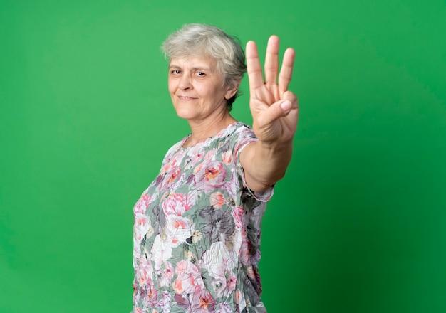 Tevreden oudere vrouw staat zijwaarts gebaren drie met hand geïsoleerd op groene muur