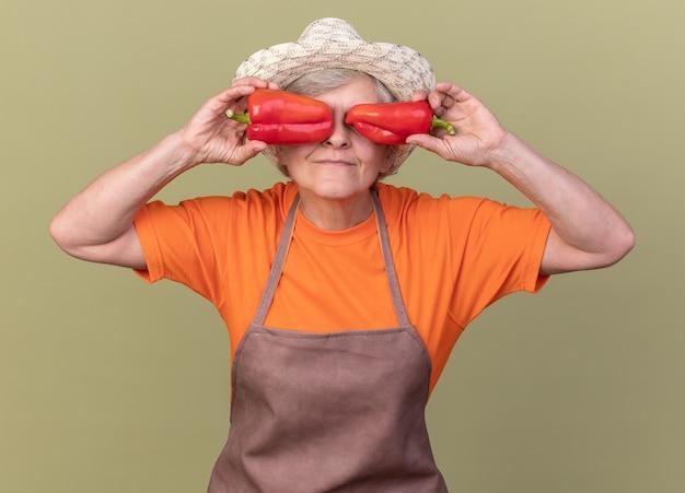 Tevreden oudere vrouwelijke tuinman met een tuinhoed die de ogen bedekt met rode paprika's geïsoleerd op een olijfgroene muur met kopieerruimte