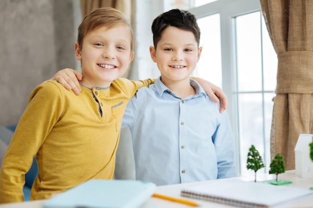 Tevreden over de resultaten. vrolijke pre-tienerjongens die elkaar knuffelen en poseren voor de camera, glimlachend helder, nadat ze klaar zijn met het werk aan hun ecologieproject