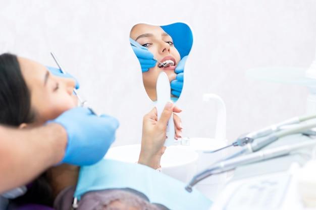 Tevreden patiënt bij de tandarts. die zijn perfecte glimlach laat zien na behandeling in de kliniek