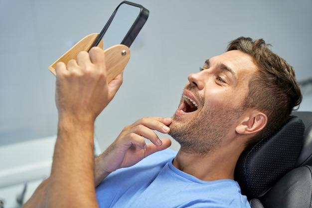 Tevreden patiënt van tandheelkundige kliniek die zijn tanden in de spiegel aanschouwt