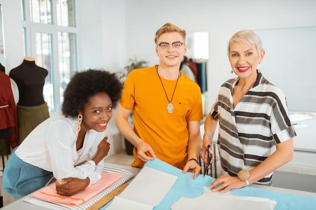 Tevreden professionele kleermakers glimlachen terwijl ze naast de snijtafel staan