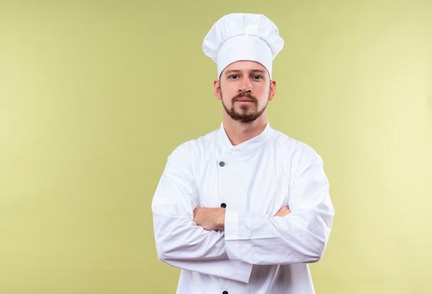 Tevreden professionele mannelijke chef-kok in witte eenvormig en kokhoed die zich met gekruiste wapens bevinden die over groene achtergrond zeker kijken
