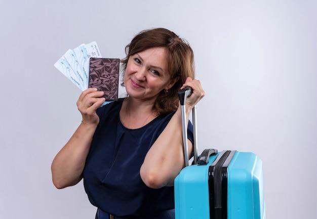 Tevreden reiziger vrouw met kaartjes en portemonnee op middelbare leeftijd met koffer op geïsoleerde witte achtergrond