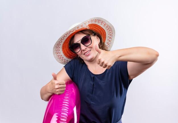Tevreden reizigersvrouw van middelbare leeftijd die glazen met hoed draagt die opblaasbare ring haar duimen tegen geïsoleerde witte muur houden
