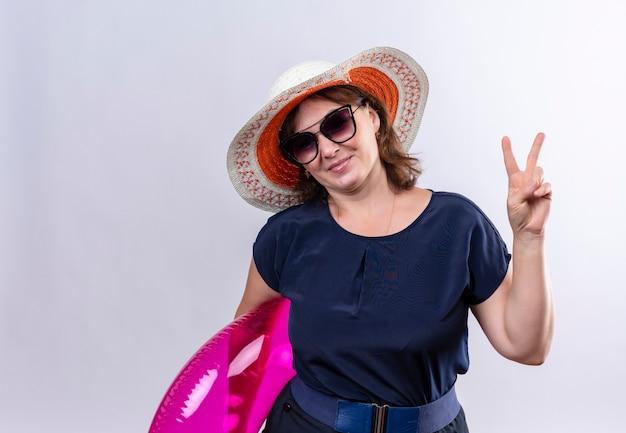 Tevreden reizigersvrouw van middelbare leeftijd die glazen met hoed draagt die opblaasbare ring houden die vredesgebaar op geïsoleerde witte muur toont