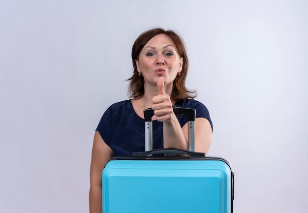 Tevreden reizigersvrouw van middelbare leeftijd die hand op koffer haar duim op geïsoleerde witte achtergrond zetten