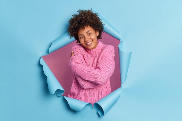 Tevreden romantische gelukkige jonge afro-amerikaanse vrouw omarmt zichzelf heeft behoefte aan warmte en liefde herinnert aan mooie herinnering draagt gebreide trui breekt door papiermuur