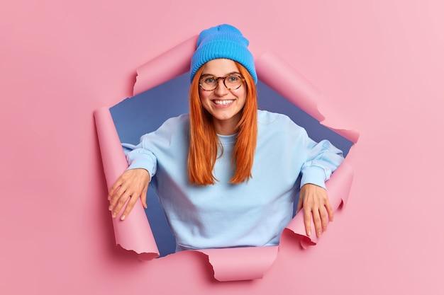 Tevreden roodharige europese vrouw glimlacht aangenaam heeft witte tanden en sproeten huid draagt blauwe hoed bril en sweatshirt staat in gescheurd gat van roze papier
