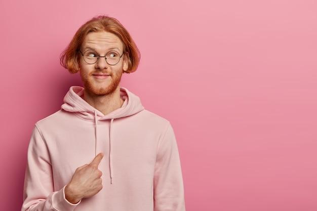 Tevreden roodharige man met kort kapsel en rood haar, wijst naar zichzelf en kijkt verwonderd opzij, draagt een optische bril en sweatshirt, vraagt 'bedoel je mij', poseert tegen een roze pastelkleurige muur