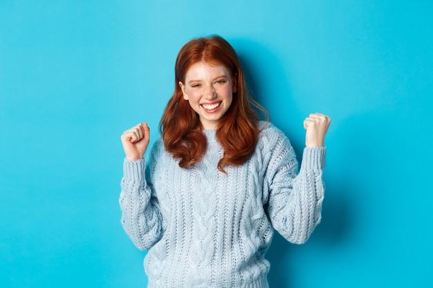 Tevreden roodharige meid bereikt doel en viert, maakt een vuistpompgebaar en glimlacht verrukt, triomfeert van de overwinning, staande tegen een blauwe achtergrond