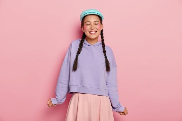 Tevreden schattig jong koreaans vrouwelijk model met rode wangen, lacht van vreugde, draagt blauwe pet, oversized trui en rok