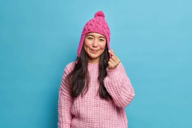 Tevreden schattige romantische aziatische vrouw maakt koreaans als teken vormt minihart aan voorkant draagt gebreide muts en trui vormt tegen blauwe studiomuur