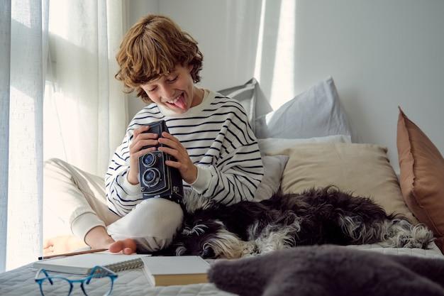 Tevreden schooljongen met oude fotocamera en pluizige hond binnenshuis