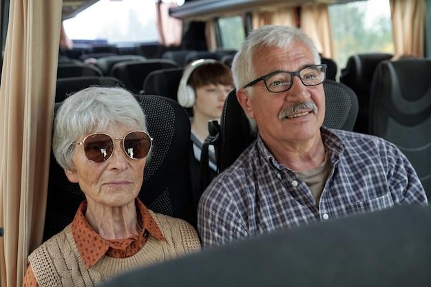 Tevreden senior kaukasisch echtpaar met grijs haar dat in de bus zit terwijl ze samen reizen
