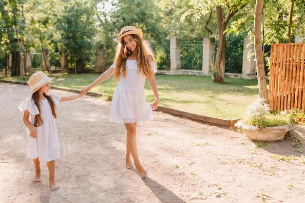 Tevreden slanke vrouw die met glimlach naar dochter kijkt en hand in hand met haar. outdoor portret van enthousiaste jonge dame blootsvoets lopen in de tuin door hek met struiken.