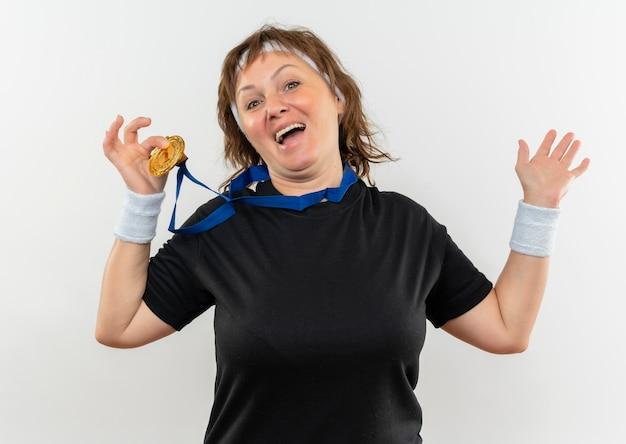 Tevreden sportieve vrouw van middelbare leeftijd in een zwart t-shirt met hoofdband en gouden medaille om haar nek en toont het glimlachend vrolijk staande over de witte muur
