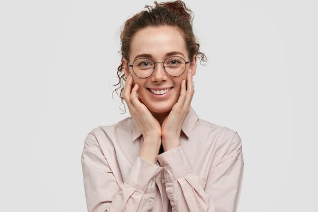 Tevreden sproeten tiener met bril poseren tegen de witte muur