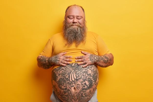 Tevreden stevige man houdt handen op buik, voelt verzadiging na het eten van een heerlijk diner, staat met gesloten ogen, geeft niet om figuur, heeft hormonale onbalans, geïsoleerd op gele muur.