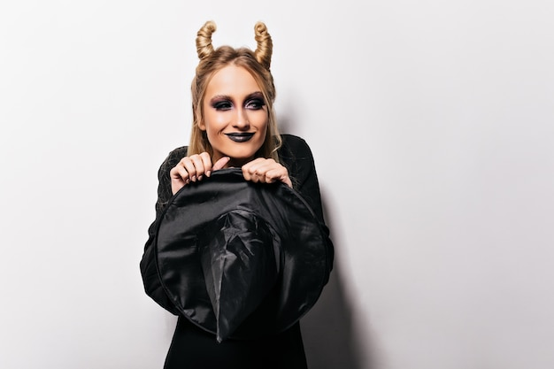 Tevreden stijlvolle vrouw in zwarte outfit die halloween viert. aanbiddelijk meisje dat in heksenkostuum voor partij voorbereidingen treft.