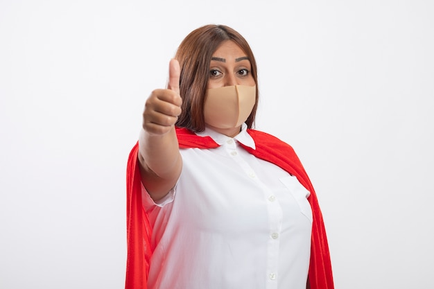 Tevreden superheldwijfje dat op middelbare leeftijd medisch masker draagt dat duim toont die omhoog op wit wordt geïsoleerd
