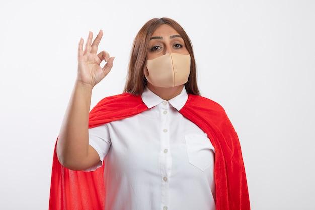 Tevreden superheldwijfje dat op middelbare leeftijd medisch masker draagt dat ok gebaar toont dat op wit wordt geïsoleerd