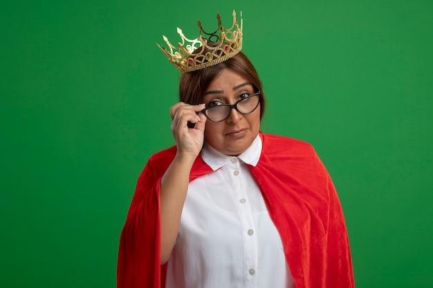 Tevreden superheldwijfje van middelbare leeftijd die een kroon dragen pakte een bril geïsoleerd op een groene achtergrond
