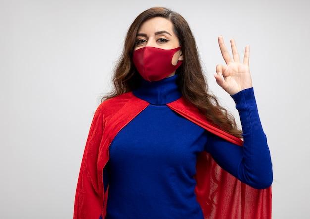 Tevreden supervrouw met rode cape die rode beschermend maskergebaren draagt ok handteken dat op witte muur wordt geïsoleerd
