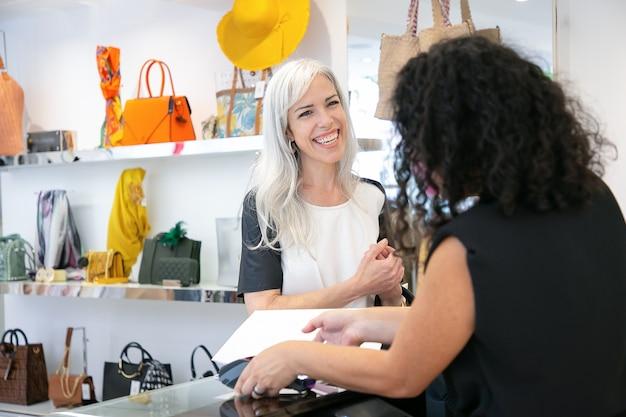 Tevreden tevreden klant die lacht tijdens het betalen bij het afrekenen. medium shot, kopie ruimte. winkelen concept
