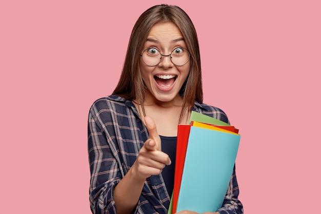 Tevreden tevreden vrouw met vreugdevolle uitdrukkingspunten rechtstreeks, drukt keuze uit