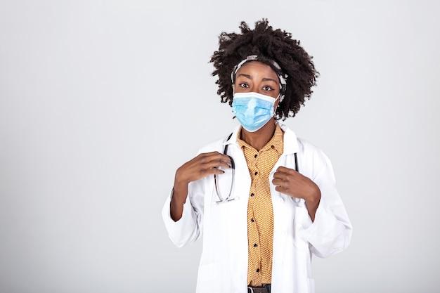 Tevreden tevreden vrouwelijke arts die de inhoudsopheffing van een beschermend gezichtsmasker draagt na het einde van de wereld