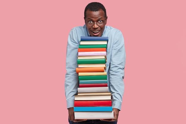 Tevreden tevreden zwarte man houdt veel boeken in handen, ziet er positief uit, gekleed in een formeel overhemd