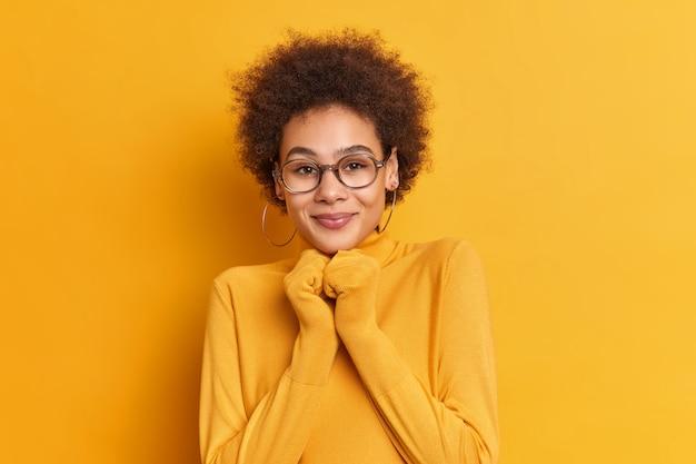 Tevreden tiener meisje met donkere huid draagt polonck met lange mouwen grote bril houdt handen onder de kin reageert op ontvangen compliment voelt zich blij en verlegen.