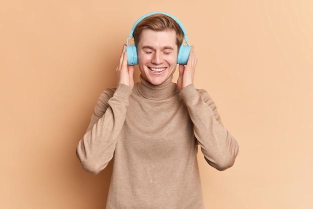 Tevreden tiener ontspant met gesloten ogen, luistert favoriete liedje via draadloze blauwe koptelefoon gebruikt muziek-app glimlacht graag draagt casual trui poses