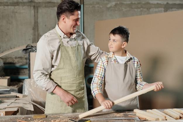 Tevreden timmerman van middelbare leeftijd in schort die trots is op tienerzoon die hem prijst voor goed werk in de werkplaats