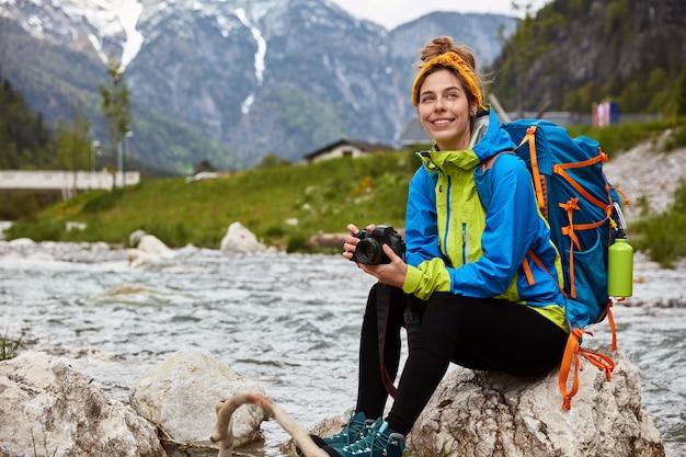 Tevreden toerist rust op rotsen, houdt fotocamera vast om foto's te maken