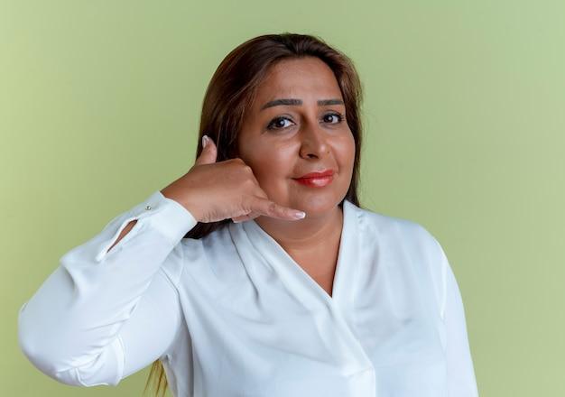 Tevreden toevallige kaukasische vrouw die op middelbare leeftijd telefoongesprekgebaar tonen