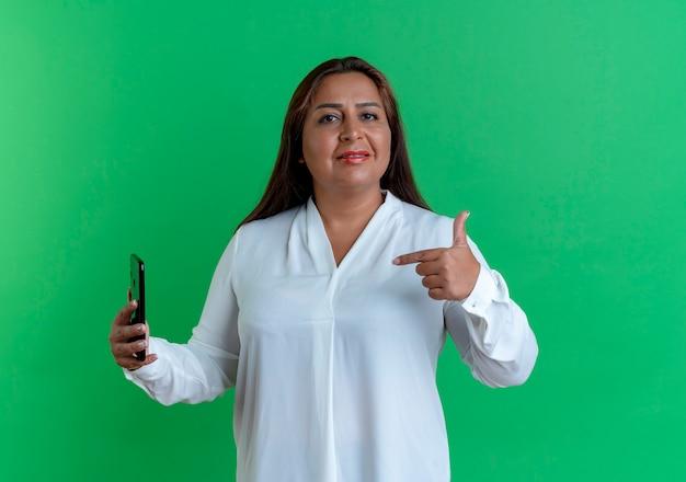 Tevreden toevallige kaukasische vrouwenholding op middelbare leeftijd en punten op telefoon
