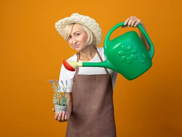 Tevreden tuinmanvrouw van middelbare leeftijd in tuinmanuniform met hoed die bloemen in bloempot met gieter water geeft geïsoleerd op een oranje muur met kopieerruimte
